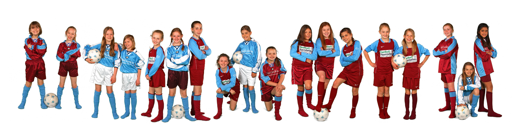 Girls school football team smiling and posing for camera